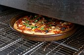 Pizza being baked in industrial oven, fast food restaurant