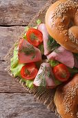 Bagel With Ham And Vegetables On Table Closeup. Top View Vertical