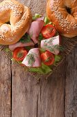 Bagel With Ham On An Old Wooden Table Top View Vertical