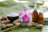 spa supplies with orchid, oil, candle , salt in bowl, spoon ,stones on banana leaf