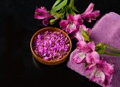 Spa and wellness setting with natural bath saltin bowl, orchid and towel