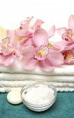 Pink orchid on towel with candles ,salt in bowl on blue towel