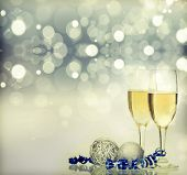 Glasses with champagne and Christmas decoration against fireworks and holiday lights