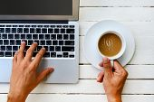 Laptop With Cup Of Coffee And Hand