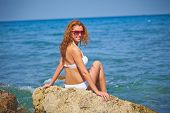 Charming girl in bikini sitting by the sea at summer resort