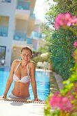 Happy female in white bikini spending leisure in pool