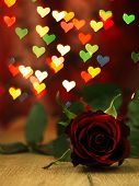 Red Rose On A Wooden Table And Hearts.