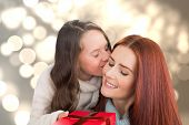 Mother and daughter with gift against light circles on bright background