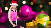 Fit festive young blonde measuring her thigh against measuring tape