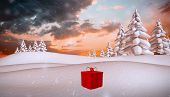 Red present against snowy landscape with fir trees
