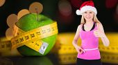 Fit festive young blonde measuring her waist against measuring tape