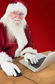Santa surfs on the internet against red background