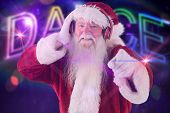 Santa is listening some music against digitally generated colourful dance text
