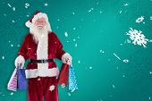 Santa carries some Christmas bags against green snowflake background