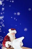 Santa reads a long list against blue