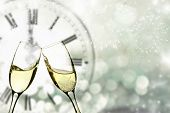 Glasses with champagne against fireworks and vintage clock close to midnight