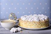 Tasty homemade meringue cake on wooden table, on blue background