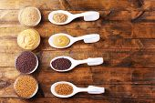 Mustard seeds, powder and sauce in spoons  and bowls on wooden background
