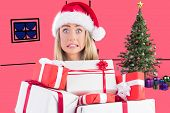 Festive blonde holding pile of gifts against pink
