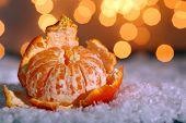 Fresh ripe mandarin on snow, on lights background