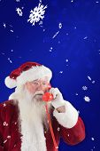 Santa on his red phone against blue snowflake background