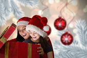 Mother and daughter opening gift against digital hanging christmas bauble decoration