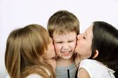 Two Girls Kissing Little Angry Boy On The Light Background