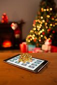 Christmas tiles against tablet with bow for christmas