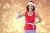 Festive fit brunette measuring her waist against yellow abstract light spot design