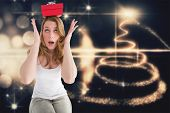 Woman balancing christmas gift on her head against christmas light design