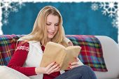WOman reading a book against blurred christmas frame
