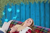 Woman asleep on couch against blurred christmas decorations hanging over wood