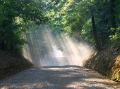 Dusty Country Road With Sunlight Rays