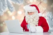 Santa using laptop against digital hanging christmas bauble decoration