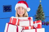 Festive blonde holding pile of gifts against purple vignette