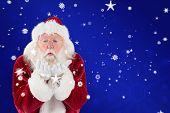 Santa Claus blows something away against blue snowflake background