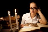 Young Girl In Glasses Over Book In Dark