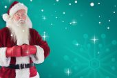 Santa Claus wears boxing gloves against green snowflake background