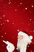 Santa claus blowing against red snowflake background