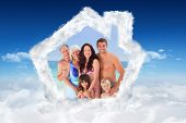 Portrait of a joyful family at the beach against bright blue sky over clouds