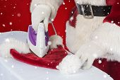 Father Christmas is ironing his hat against red snowflake background