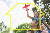 Boy with toy aeroplane sitting on fathers shoulders against house outline