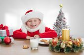 Cute boy smiling against christmas tree in bright room