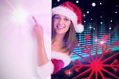 Pretty girl in santa costume showing card against digitally generated disco light design