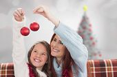 Mother and daughter holding baubles against blurry christmas tree in room