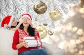 Mother and daughter with gift against christmas decorations on branch