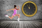Composite image of fit brunette running against grey room