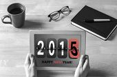 Businesswoman holding tablet at desk against happy new year 2015