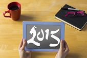 Businesswoman using tablet at desk against 2015 year of the ram
