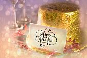 Digital composite of Happy new year card leaning on gold party hat